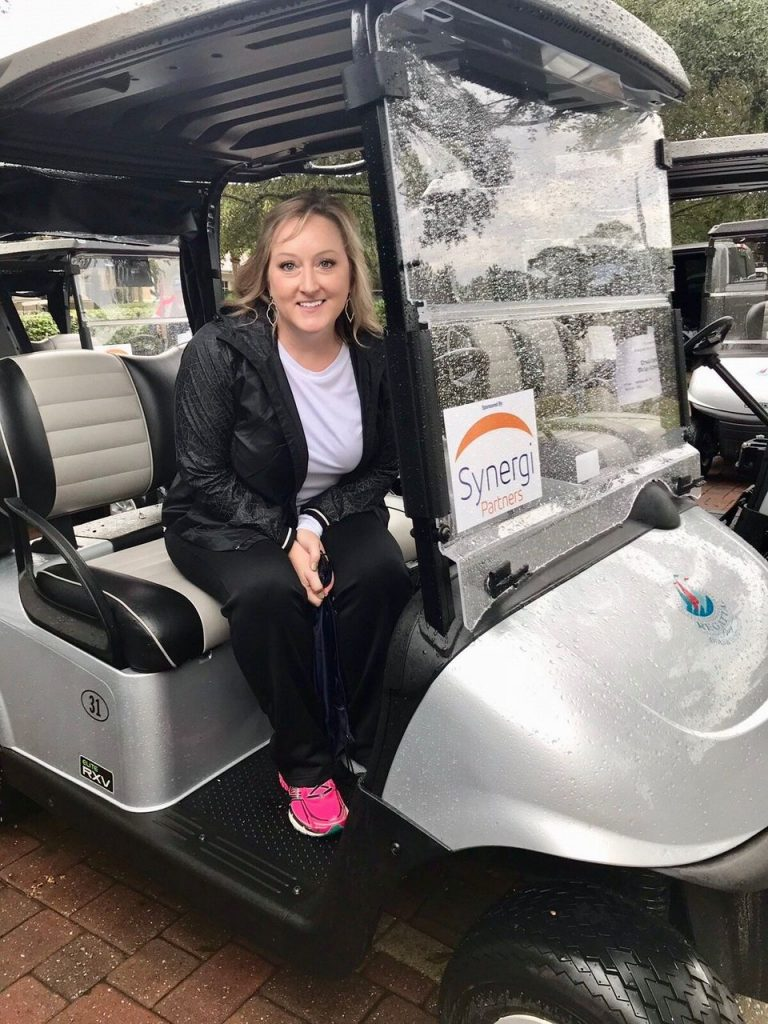 Karen Freeman, Synergi Partners Global Sales Manager in a golf cart