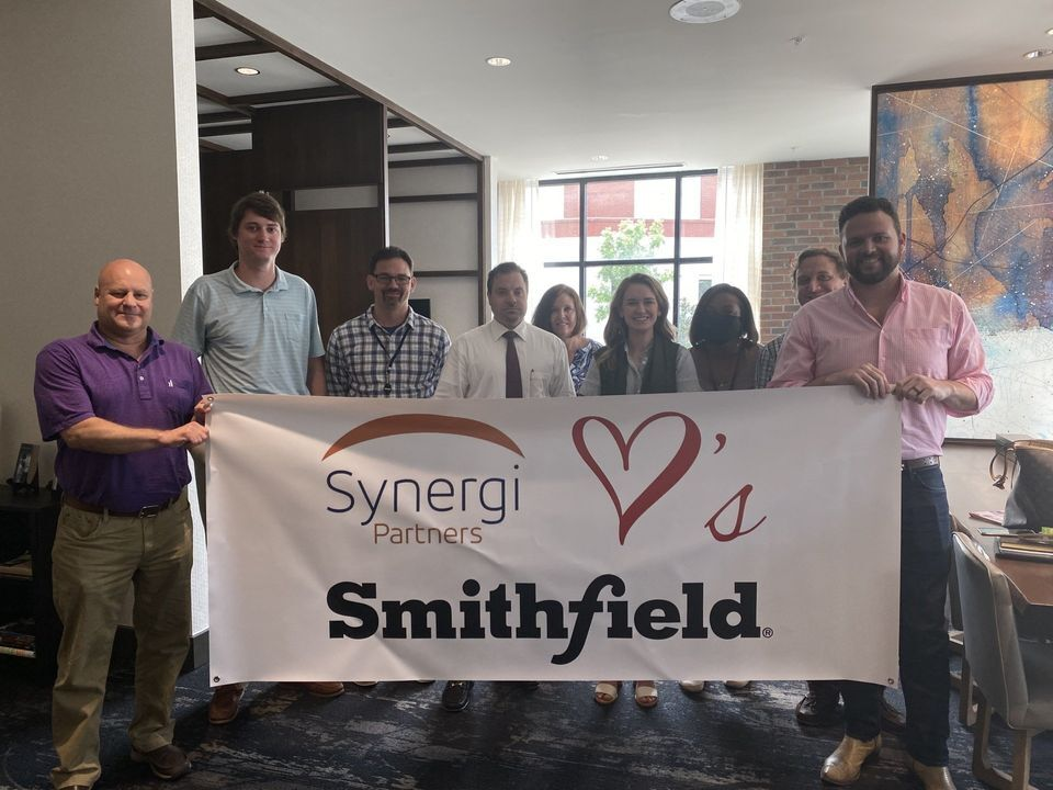 """Team of Smithfield are holding a banner that says """"Synergi Partners love's Smithfield"""""""